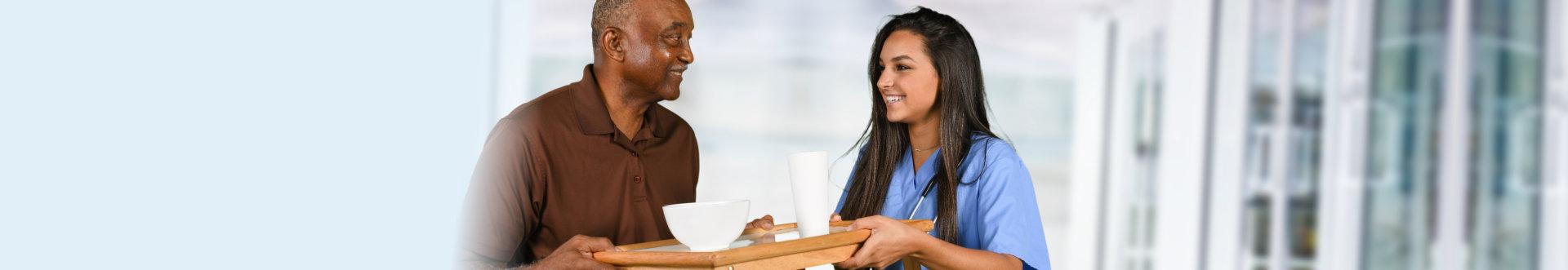 nurse serving food to old man